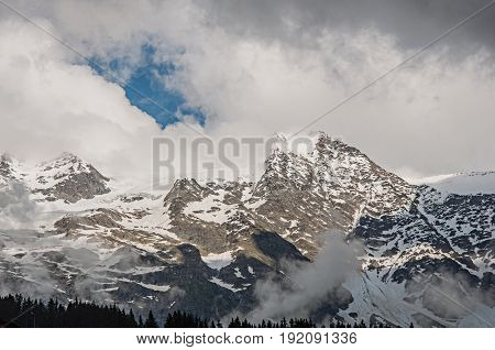 View of snowy peaks in Les-Contamines-Montjoie, French Alps, alpine mountains landscape, blue sky and clouds