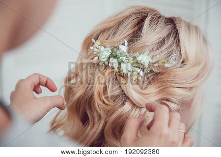 Hair stylist makes styling with hair accessory.