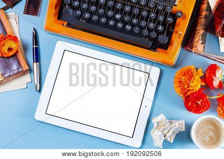 Workspace with orange retro typewriter, copy space on modern tablet
