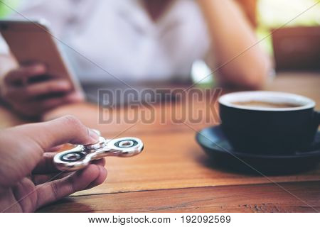 A hand holding and playing metal silver color fidget spinner with coffee cups and people using mobile phone in background