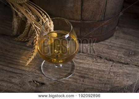 Glass of Cognac and old oak barrel defocussed.