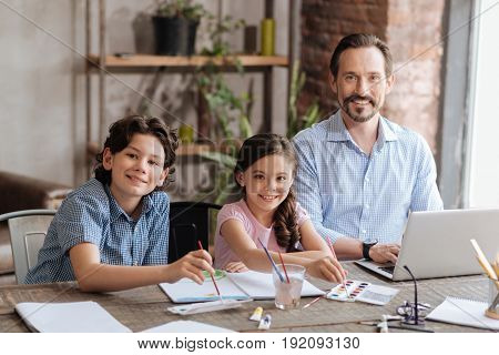Appreciating time together. Adorable single-parent family sitting at the table and smiling at the camera, being happy to be together, with kids painting a picture and dad working