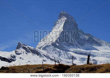 The peak of the Matterhorn in Switzerland with a fence in the foreground.