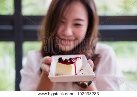 A beautiful Asian woman holding and showing blueberry cheese cake with feeling happy and good lifestyle in modern cafe
