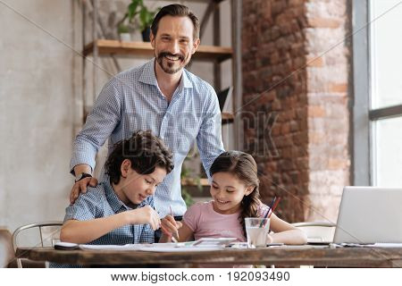 Adorable kids. Happy young father laying his hands on the shoulders of his little children while they painting a picture with watercolors