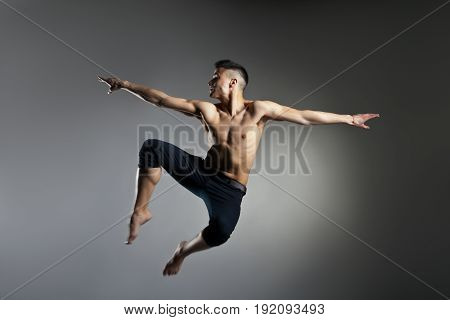 Caucasian man gymnastic leap posture on grey background