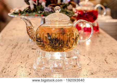 Glass teapot with green tea on a stand