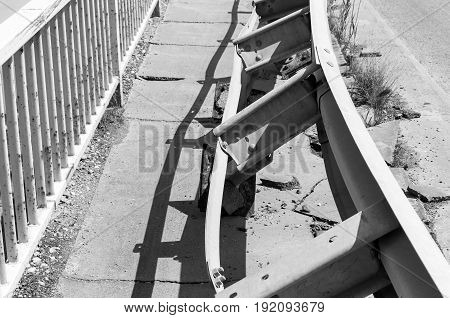 Damaged security steel fence on the bridge from car crash accident. Selective focus. Black and white.