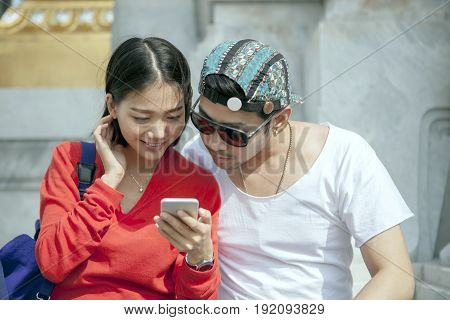couples of asian younger man and woman looking to smart phone in traveling destination