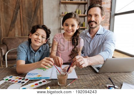 Broad smiles. Cheerful adorable family sitting at the table and washing brushes in the glass of water while posing for the camera and smiling sincerely