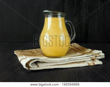 Yellow fruit juice in a glass jug standing on a towel on a black background