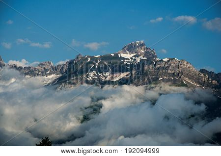 View of snowy peaks in Saint-Gervais-Les-Bains, French Alps, alpine mountains landscape, blue sky and clouds