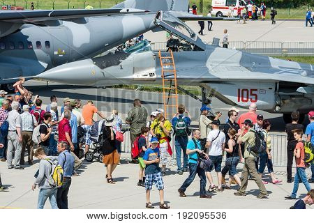 BERLIN GERMANY - JUNE 03 2016: Visitors and guests of exhibition and multirole fighter Mikojan-Gurewitsch MiG-29 in the background. Exhibition ILA Berlin Air Show 2016