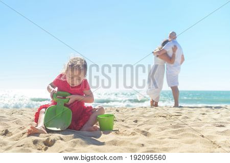 Girl in red dress digging in sand on the beach, blurred happy parents holding hands on background, young romantic couple, life with kids