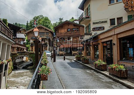 Megève, France - June 25, 2016. View of street with shop buildings, creek and cloudy sky. Megève is a famous ski resort located in Haute-Savoie Province, near the Mont Blanc in the French Alps