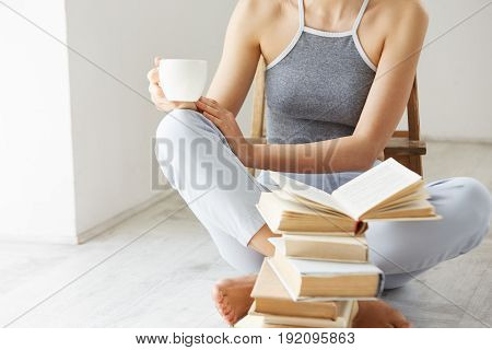 Close up of young girl  holding book cup of coffee sitting on floor with books over white wall early in morning. Copy space.