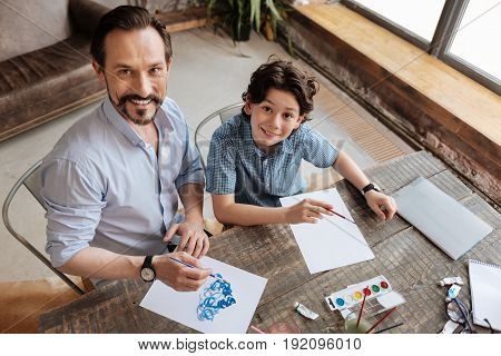 Father-son ties. Adorable wavy-haired boy sitting at the table next to his father, painting pictures while both of them looking up at the camera and smiling sincerely