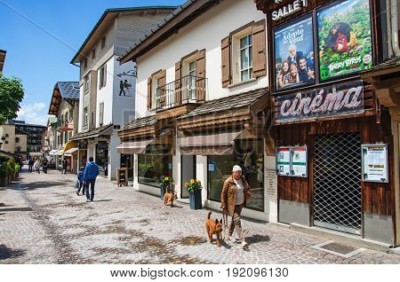 Megève, France - June 25, 2016. View of street with shop, cinema and madam with dog in Megève, a famous ski resort located in Haute-Savoie Province, near the Mont Blanc in the French Alps