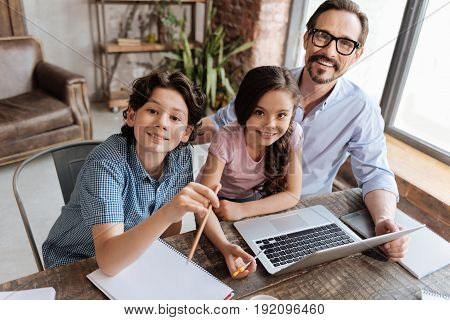 New generation. Happy sweet single-parent family sitting at the table in living room and studying with the use of educational videos while smiling at the camera