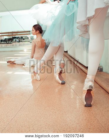 Thr seven ballerinas at ballet rack in the rehearsal hall of the theater