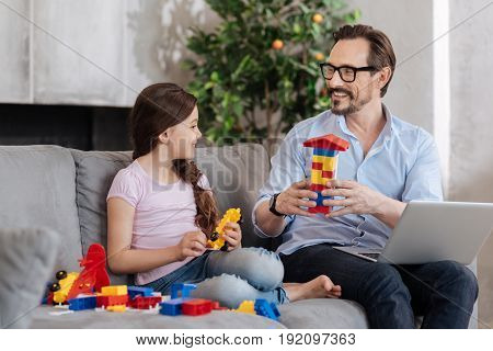 Pleasant discussion. Petite gorgeous girl and her pleasant young father sitting on the sofa and discussing their new erector set while holding some pieces of it each