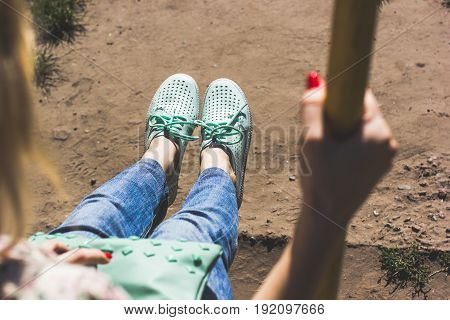 Young woman with red nails is swinging on a swing in summer park