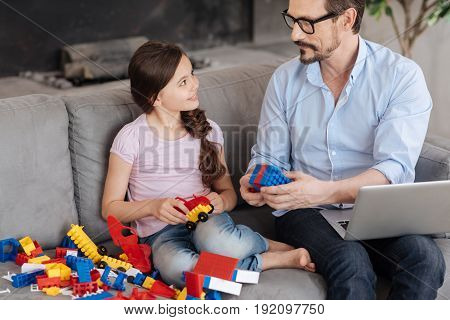 Symbol of togetherness. Handsome young father sitting on the sofa next to his daughter and showing her how two pieces of erector set match