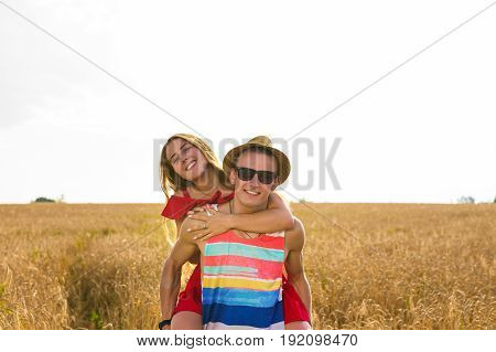 Happy Couple Having Fun Outdoors on wheat field. Laughing Joyful Family together. Freedom Concept. Piggyback.