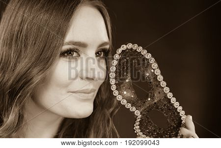 Holidays people and celebration concept. Closeup woman face with carnival venetian mask on dark background black and white photo