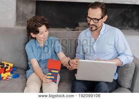 Happy together. Pleasant young father sitting on the sofa with his laptop on the lap and touching the hand of his son holding a tower built with an erector set