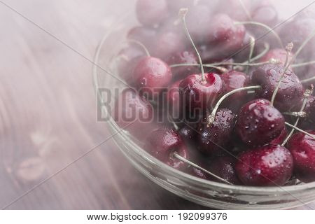 A bright ripe cherry covered with droplets of water lies in a transparent bowl in a cold steam on a brown wooden background