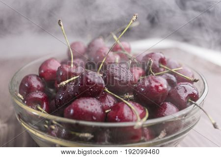 Juicy ripe sweet cherry covered with drops of water and cold steam lies in a transparent bowl