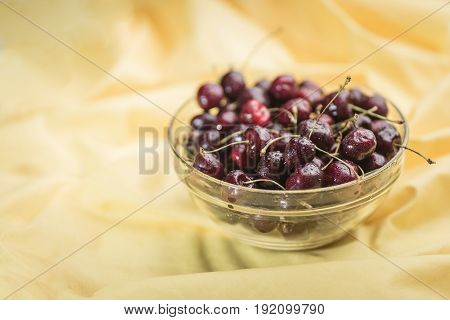 Fresh juicy cherry covered with droplets of water lies in a transparent bowl on a light golden background