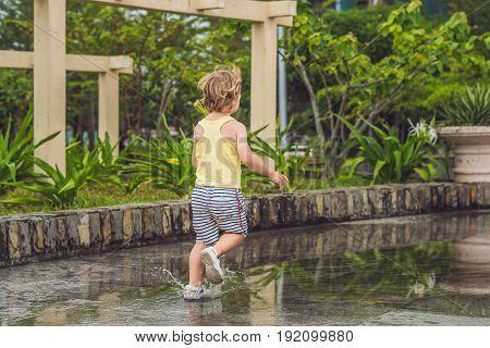 Little Boy Runs Through A Puddle. Summer Outdoor