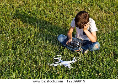 Little boy sitting on the grass with drone and remote controller