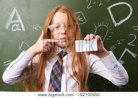 Schoolgirl with business card, schoolgirl with glasses, schoolgirl on background of board.