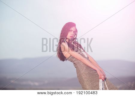 woman or cute girl fashionable model standing with white strings in long brunette hair hairstyle in grey dress on light sky on mountain landscape. Fashion and beauty. Wanderlust