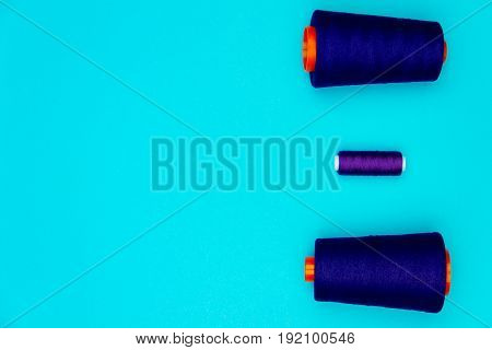 Two big sewing spools and a small one isolated on blue background.