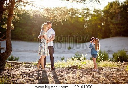Happy family rest on nature, girl photographs her father and mother