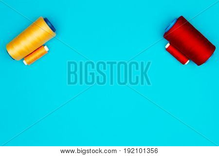 Colorful sewing spools of different size isolated on blue background.