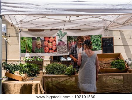 Asbury Park NJ USA -- June 18 2017 A man assists a woman shopper at a Farmers Market produce stand in Asbury Park NJ. Editorial Use Only