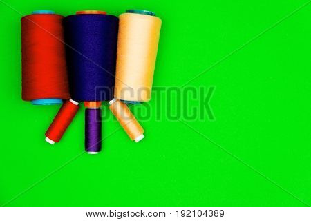 Colorful sewing spools of different size isolated on green background.