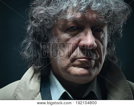 The senior man in cloak as detective or mafia boss. Studio shot on gray in retro stile. The male face close up poster