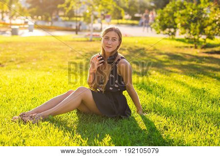 Girl with headphones in summer on a meadow