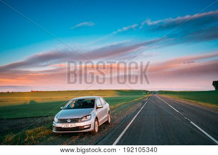 Gomel, Belarus - May 11, 2017: VW Volkswagen Polo Vento Sedan Car Parking Near Asphalt Country Road In Sunny Morning Or Evening. Road At Sunny Sunset Or Sunrise Under Dramatic Sky At Spring Or Summer