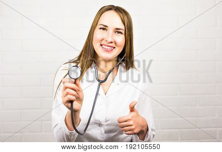 Happy female doctor using stethoscope and gesture thumbs up.