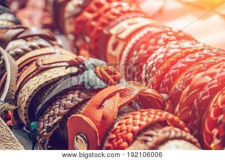 Braided handmade leather bracelets in sunlight, toned