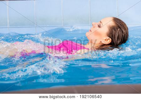 Woman In Pink Swimsuit Swimming In Blue Pool On Her Back