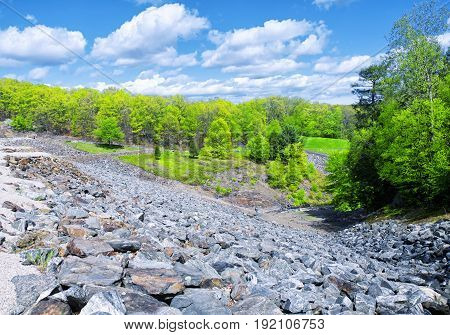 The rocky side of Hop Brook Dam in Naugatuck connecticut on a sunny blue sky day.