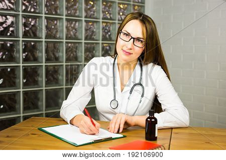 Female physician medicine doctor or pharmacist sitting at work table, holding jar or bottle of pills in hand and writing prescription on special form. Medical care, pharmacy or health insurance concept